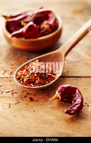 Wooden spoon with red chili pepper flakes and whole red peppers - Stock Photo