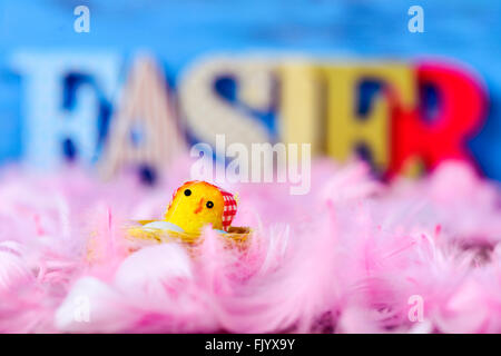 closeup of a yellow toy chick surrounded by soft pink feathers and three-dimensional letters forming the word easter - Stock Photo