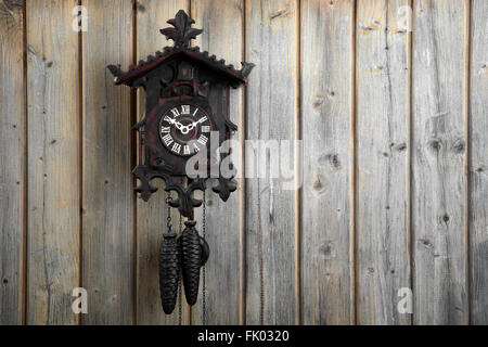Old Black Forest cuckoo clock, on a wooden wall, Germany - Stock Photo