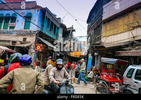 Pedestrians, motor bikes and cars in the narrow streets of Delhi, India, Asia - Stock Photo