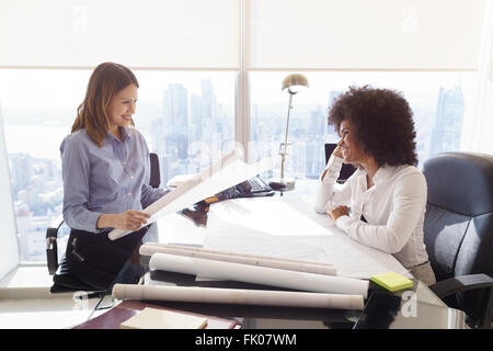 Team of two female architects, sitting at desk in office. The women talk and smile reviewing a building plan. Medium - Stock Photo