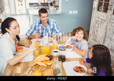 Happy family eating breakfast at table in house - Stock Photo