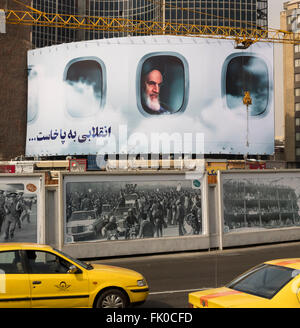 Shown seated in airplane returning him to Iran, Ayatollah Khomeini looks down on traffic in Valiasr Square, Tehran - Stock Photo