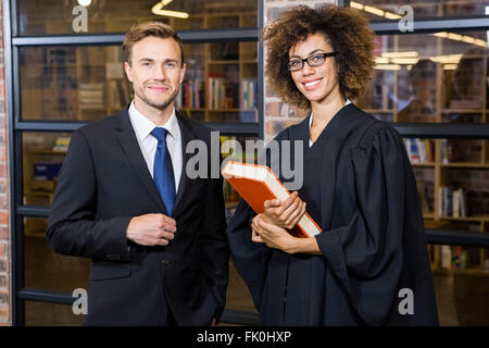Businessman standing with lawyer near library - Stock Photo
