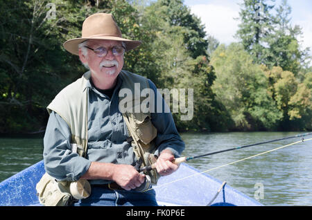 Portrait of a happy retired senior man spending time on the water fishing. - Stock Photo