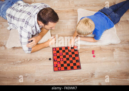 Father and son playing checker game while at home - Stock Photo