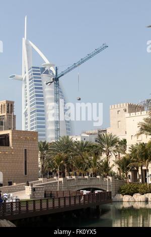 Dubai's symbol Burj Al Arab hotel photographed along with construction crane - Stock Photo