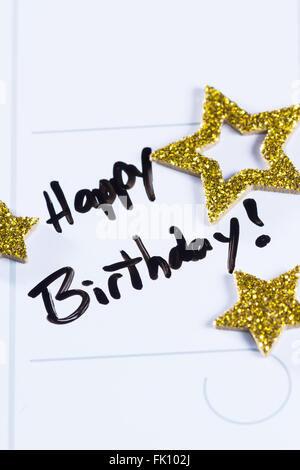 close up of a calendar with the words happy birthday written on it and then decorated with gold stars - Stock Photo
