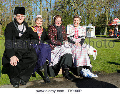 The Keukenhof, a tourist attraction in the Netherlands. People in traditional Dutch costumes sitting on a bench. - Stock Photo