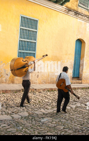 Two musicians carrying their instruments on their way to work in the colonial town of Trinidad, Cuba - Stock Photo