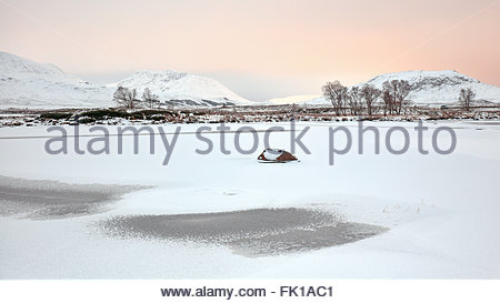 Snow covered mountains and a solitary rock on a frozen Loch Ba on a cold winter morning. - Stock Photo