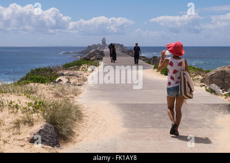 A female tourist in a watermelon top and watermelon coloured hat walking along the causeway at Nobby's Head, Newcastle - Stock Photo