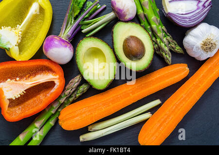 Sliced fresh vegetables on a dark board, top view, flatly, avocado, bell peppers, onion - Stock Photo