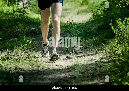 male athlete running through a summer forest, body parts foot - Stock Photo