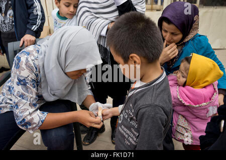 Volunteer doctor treating refugees from Syrian and Afghnanistan in Çesme, near Izmir, Turkey. They are all waiting - Stock Photo