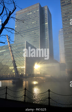 JP Morgan tower block rising above winter fog clearing from Canary Wharf waterways with sun reflecting on glazing - Stock Photo