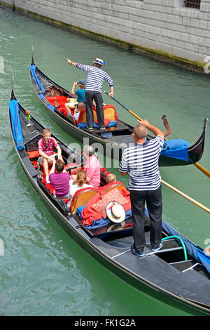 Venice gondola family group of tourists taking a sightseeing tour ride along narrow canal with gondolier pointing - Stock Photo