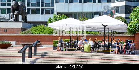 Visitors at tables in  piazza of British Library in London Camden England UK overlooked by the Newton bronze statue - Stock Photo