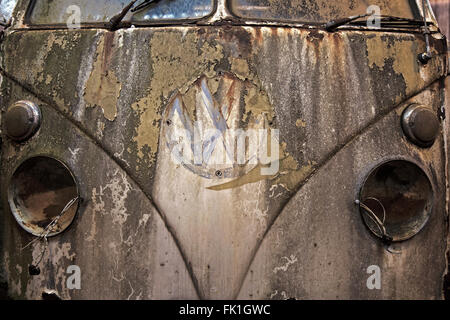 Front of an old Volkswagen Camper van, with peeling paint and missing headlights. - Stock Photo