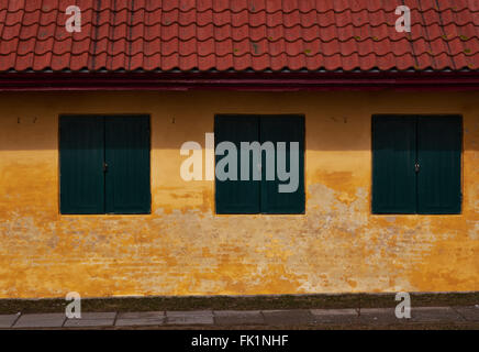 Three green wood shutters in a yellow plastered brick facade of an old house with red roof tiles - Stock Photo