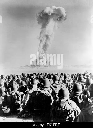Nuclear Explosion. Troops from 11th AB Division in front of a  mushroom cloud from a nuclear test explosion at Frenchman - Stock Photo