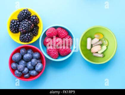Berries and dietary supplements in colorful bowls viewed from above, on blue surface - Stock Photo