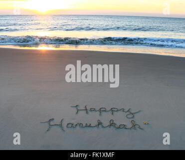 Happy Hanukkah written in sand on the beach - Stock Photo
