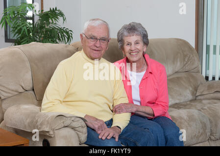 Portrait of a happy couple in their mid-eighties in their home. - Stock Photo