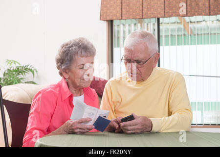 An elderly couple are bewildered as they try to navigate the instructions for their new phone. - Stock Photo
