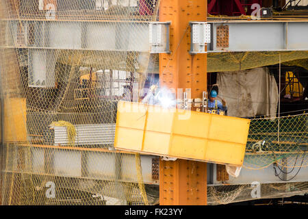 Construction workers welding on building site - Stock Photo