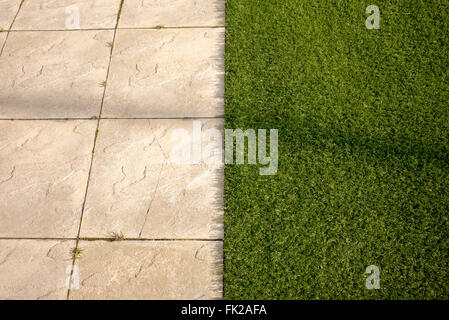 Artificial grass / astro turf meets paving slabs on a new build housing estate. Bicester, Oxfordshire, England - Stock Photo