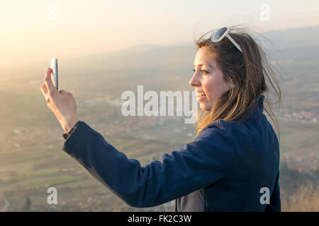 Girl taking a selfie on a hiking trip at sunset - Stock Photo