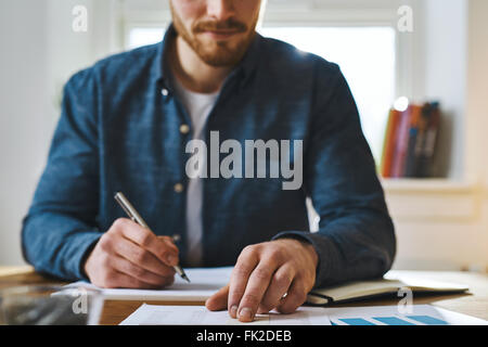 Cropped view of unidentifiable man in blue shirt with hand over paperwork as if to check statistics or plan something - Stock Photo