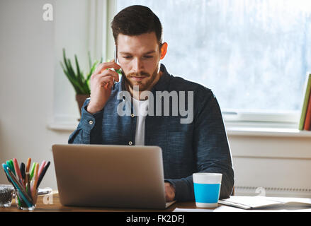 Concentrated entrepreneur working on laptop talking on phone - Stock Photo
