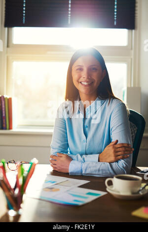 Portrait of business woman sitting at her desk in a office smiling at the camera - Stock Photo