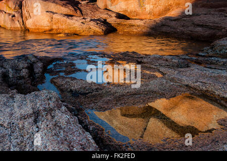 At Ploumanach the huge granit boulders by the seaside are lit with warm afternoon light - Stock Photo