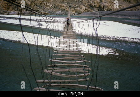 Man crossing the Hussaini bridge in Passu, old suspension bridge, above the Hunza River in Hunza Valley, Pakistan. - Stock Photo