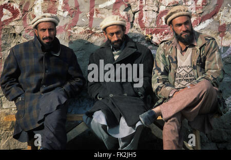 Three Pakistani men sitting on a bench in the village of Karimabad, Hunza Valley, Pakistan. - Stock Photo
