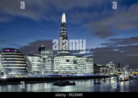 The London skyline in Southwark showing the Shard and City Hall, at night - Stock Photo
