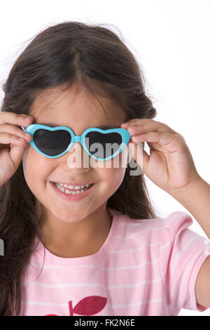 Little Girl Is Wearing Heart Shaped Sunglasses on white background - Stock Photo
