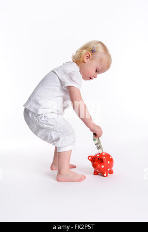 Toddler girl is putting a dollar in a piggy bank on white background - Stock Photo