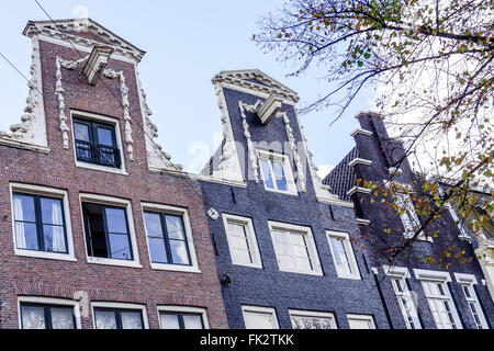 Step Gable and Raised Neck Gables with Hoists on houses along a canal in Amsterdam - Stock Photo