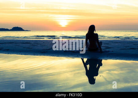 Silhouette of a beautiful young girl sitting on sea beach at sunset. - Stock Photo