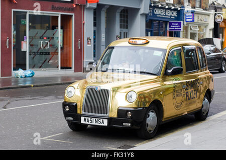 Golden Hackney Cab parked in London - Stock Photo