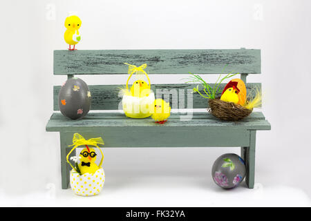 Composition with chick figurines and easter eggs, placed in a bench - Stock Photo