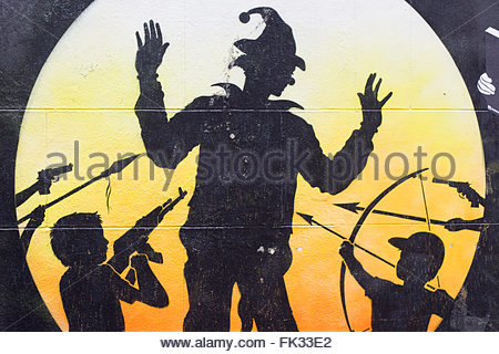 Approved Wall Art Graffiti in Brick Lane London 'clown/scarecrow held up at sunset by children's with Weapons' - Stock Photo