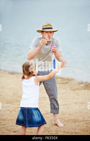 Father and child on vacation playing with soap bubbles on beach - Stock Photo