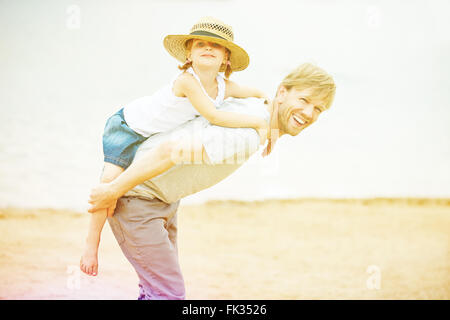 Happy father giving his daughter a piggyback ride on beach in summer - Stock Photo