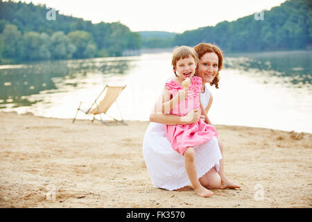 Happy girl with ice cream and mother in summer vacation at a lake - Stock Photo