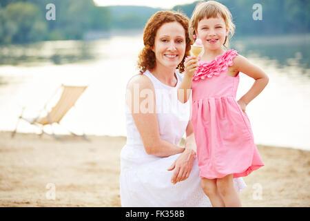 Happy child eating ice cream cone on beach in summer